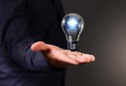 Human hand holding a shining electric bulb